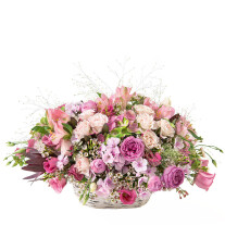 romantic basket of seasonal flowers in various shades of pink , with roses included.